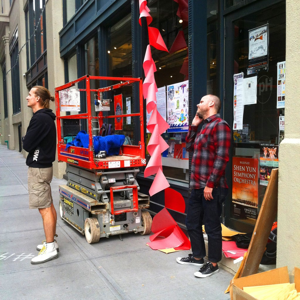 """Goen oversees the hanging of """"Who Is Chelsea Manning"""" a few short hours before the festival began."""