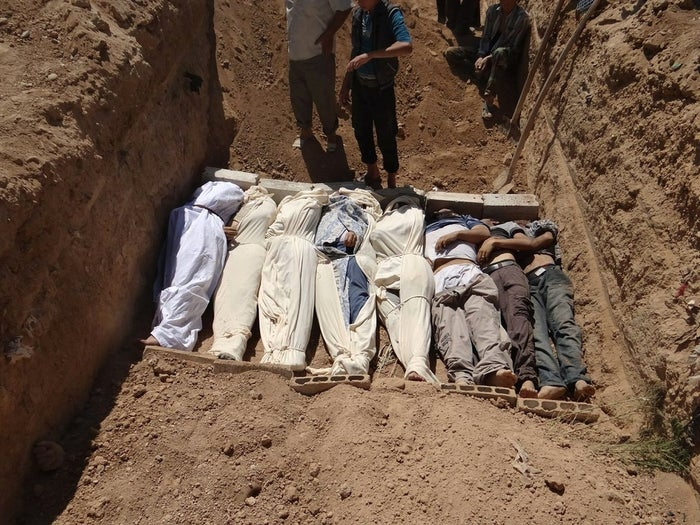 Several bodies are buried in a suburb of Damascus, Syria, during a funeral on Wednesday, Aug. 21, 2013.