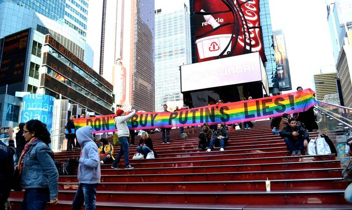 """Activists unfurled a banner reading, """"Don't buy Putin's lies!"""" on steps above TKTS Times Square in New York City."""