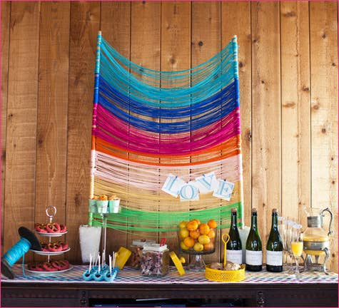 Wrap colored yarn around two dowels for a bright table or photobooth backdrop.