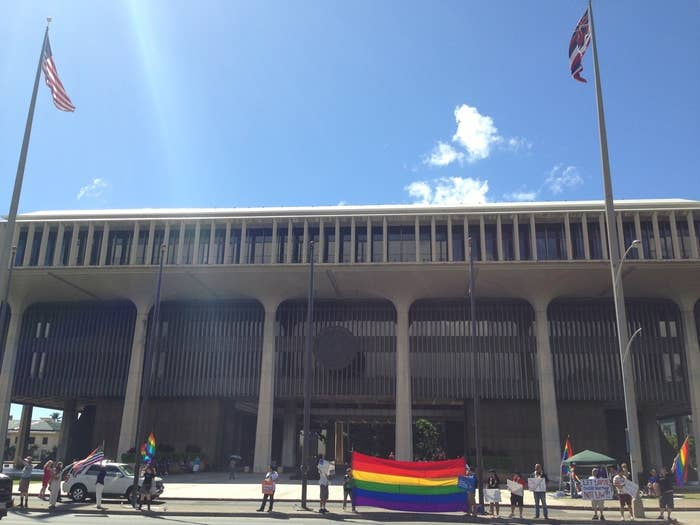 Sign wavers in support of marriage equality stand outside of the Hawaii State Capitol Monday.