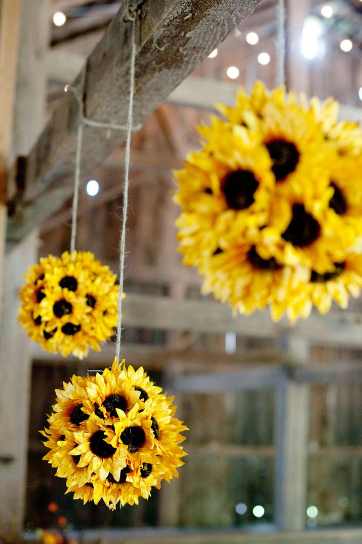 You can use fake flowers since a) sunflowers are convincing and b) they'll be hanging from the ceiling so they're less likely to be seen up close. All you need are fake sunflowers and styrofoam balls from the craft store.