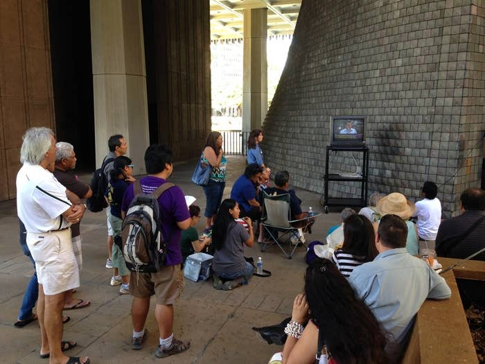People watch the joint committees hearing on TV from the Hawaii State Capitol rotunda Monday.