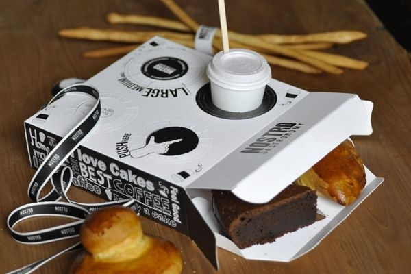 A pastry box with built-in coffee holder.