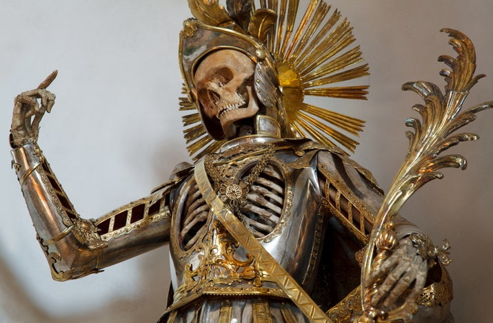 """He wear armor because he was believed to have been an Early Christian soldier who was martyred. The current suit of armor was made by a silversmith in Augsburg, Germany, in the 18th century. The skeleton was vandalized in the 20th century -- its skull was stolen, but later returned and placed back in its helmet."""