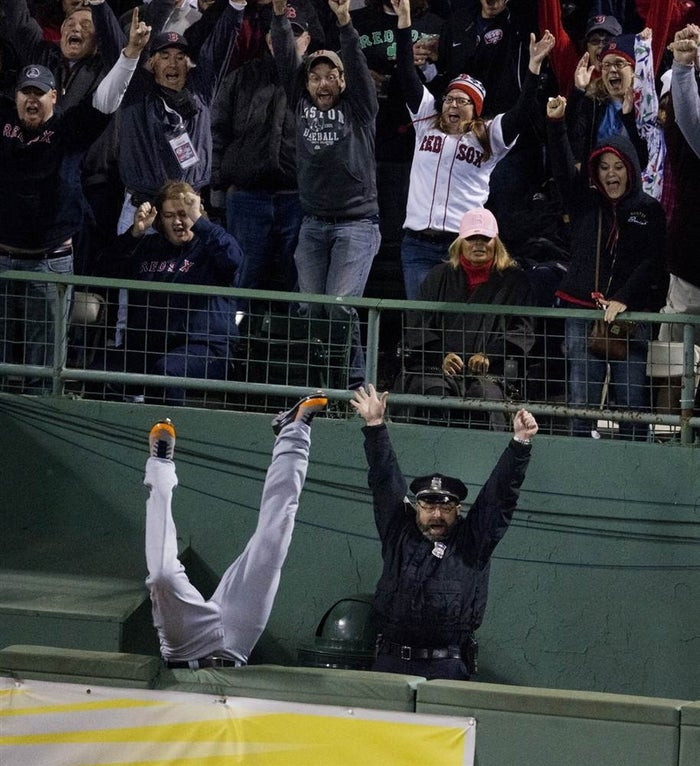 Steve Horgan, the most famous stadium cop in history, raises his arms in exaltation as Detroit's Torii Hunter flips into the bullpen and David Ortiz's eighth-inning home run in Game 2 of the American League Championship Series ties a critical game the Red Sox would later win.