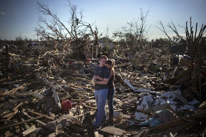 Um casal faz uma pausa enquanto tenta salvar os restos do lar de um membro da família um dia depois de um tornado ter devastado a cidade de Moore, estado de Oklahoma, EUA.