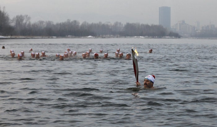 Nikolay Petshak carries the Olympic torch as he leads a group of members of local winter swimming clubs during the Sochi 2014 Winter Olympic torch relay in the waters of the Yenisei River in Russia's Siberian city of Krasnoyarsk, November 26, 2013.