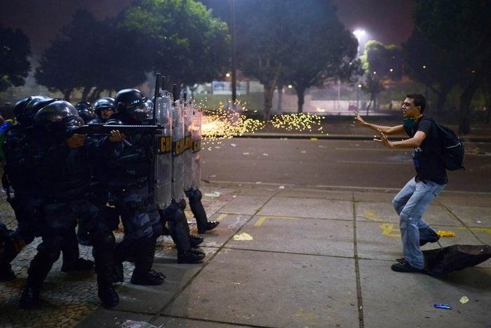 Um manifestante é alvejado com balas de borracha como reação da polícia de choque após confrontos iniciados durante protestos contra a corrupção e os aumentos de preços, no Rio de Janeiro, Brasil.