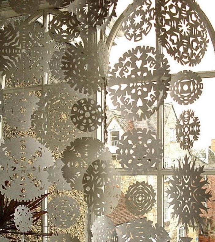 While your snowflakes don't have to look this ornate, doilies are cheap and make fancy snowflakes with a little extra clipping.Use fishing line to hang them and let it snow.
