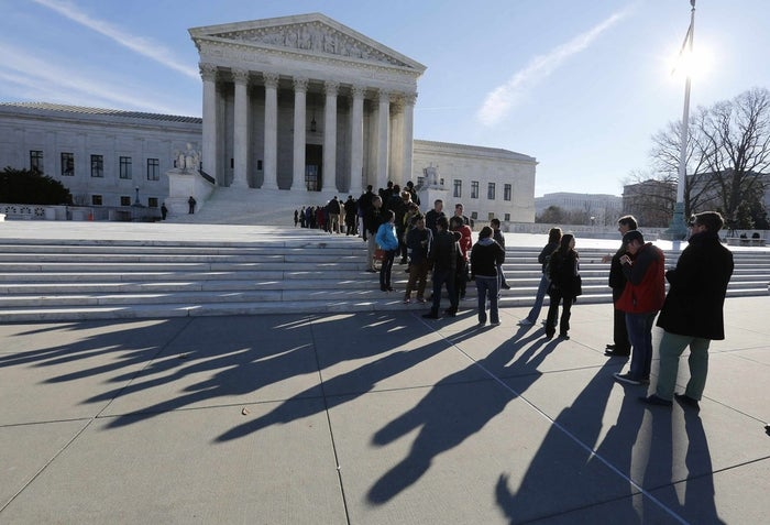 Members of the public cast shadows as they line up in front of the U.S. Supreme Court in Washington January 13, 2014.