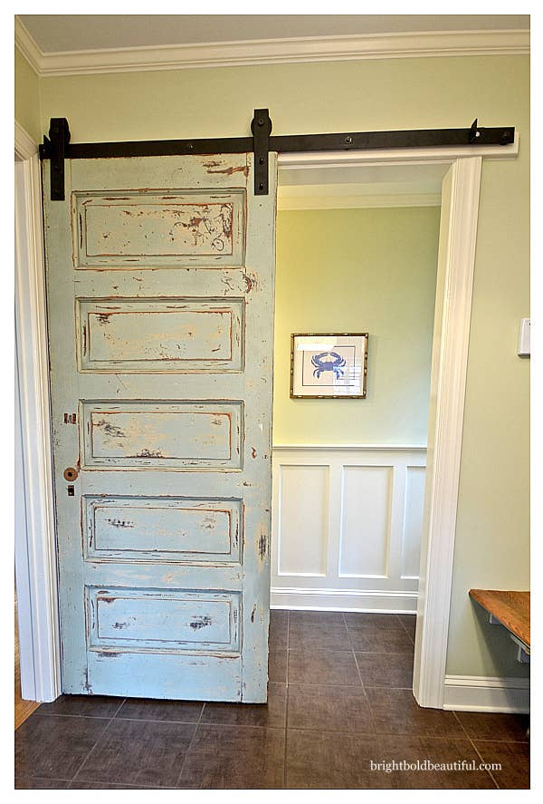 A rugged barn door plays an updated role in a bedroom entranceway.