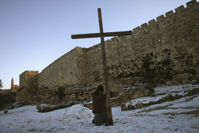 A visitor places a cross in the snow as he prays for peace near the old city wall of Jerusalem.