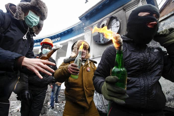 Pro-European integration protesters carry Molotov cocktails during clashes with police in Kiev Monday.