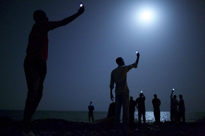 "In this photo, titled ""Signal,"" African migrants on the shore of Djibouti city at night, raise their phones in an attempt to capture an inexpensive signal from neighboring Somalia—a tenuous link to relatives abroad.Djibouti is a common stop-off point for migrants in transit from such countries as Somalia, Ethiopia and Eritrea, seeking a better life in Europe and the Middle East."