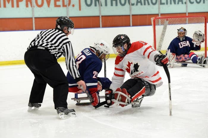 Sled hockey players battle at eye level with two sticks, sharp sled runners, and serrated ice picks.
