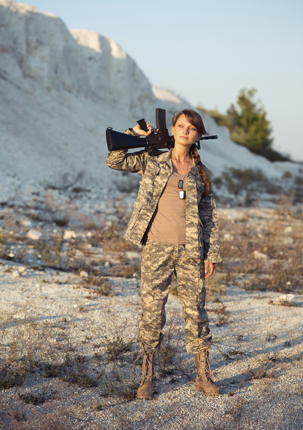 "That is followed by this picture, with the caption: ""Young beautiful female soldier dressed in a camouflage with a gun in the location."""