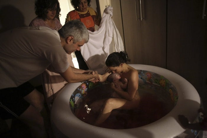 A Brazilian woman gives birth at home in a small pool. A United Nations human rights body has ruled that discrimination and structural inequalities in Brazil result in varying degrees of quality of and access to maternal health care in the country.