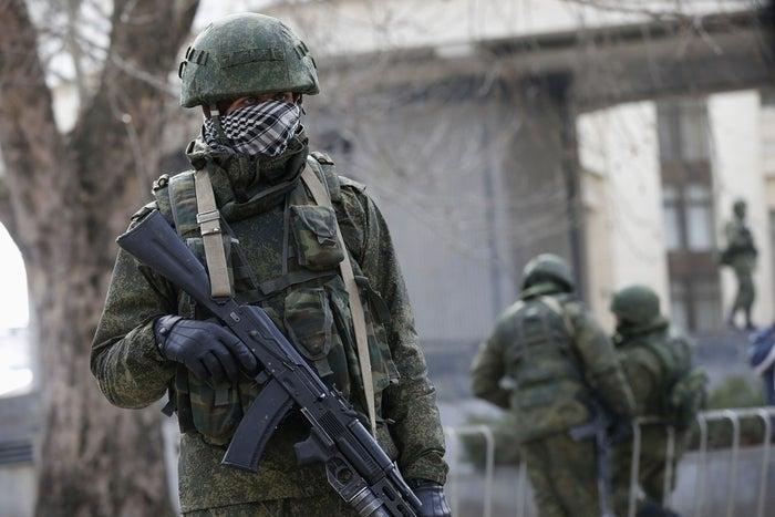 Armed men patrol the regional parliament building in the Crimean city of Simferopol on Mar. 1.