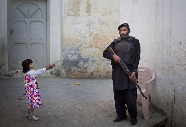 Uma jovem garota chega a um policial paquistanês em Mingora, Swat Valley, Paquistão.  15 de novembro de 2012.