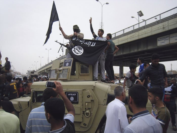 Al-Qaeda fighters celebrate on vehicles taken from Iraqi security forces, on a main street in Fallujah, west of Baghdad on March 30.