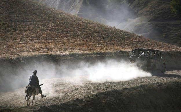 Um afegão segue um comboio de soldados alemães na região montanhosa de Feyzabad, a leste de Kunduz, no Afeganistão.  15 de setembro de 2009.