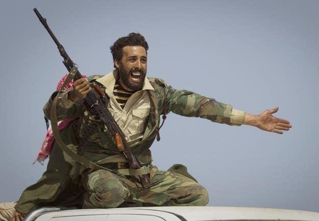 Um rebelde líbio a leste de Sirte, no centro da Líbia, enquanto as forças de Gadafi começam a bombardear a área.  29 de março de 2011.