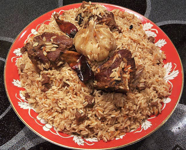 """A delightful mixture of rice, bits of meat, grated carrots and onions, and raisins (with a clove of roasted garlic on top). The """"wedding"""" part refers to the fact that it's easy to cook in large quantities (traditionally in a kazan over an open fire) and is often served on special occasions, like weddings."""