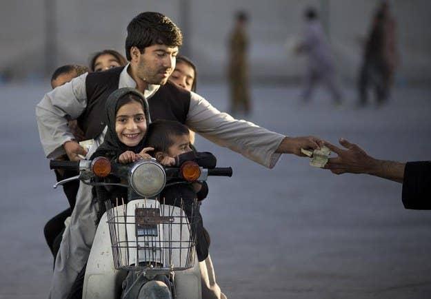 Um homem afegão com seus cinco filhos paga dinheiro para entrar em um parque em Kandahar, no sul do Afeganistão.  1º de novembro de 2013.