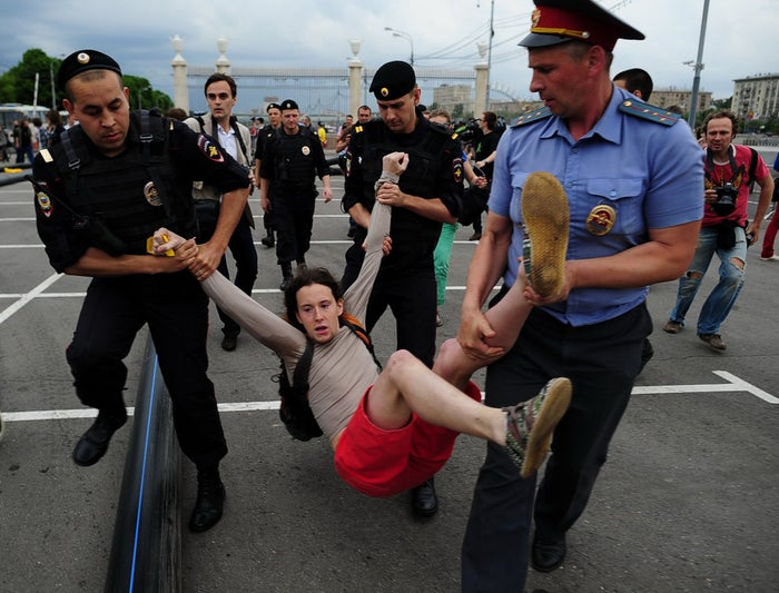 A young man is detained by the police during a protest by LGBT rights activists in Gorky Park, Moscow on May 25, 2013.