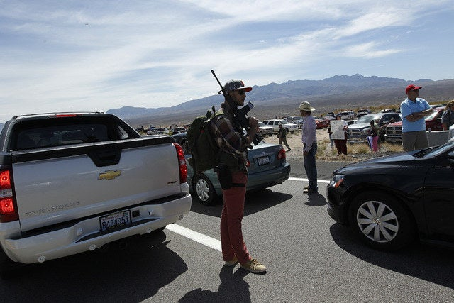 Tyler Lewis, from St. George, Utah, stands in the middle of northbound I-15 with his gun while gathering with other supporters of the Bundy family to challenge the Bureau of Land Management Saturday.