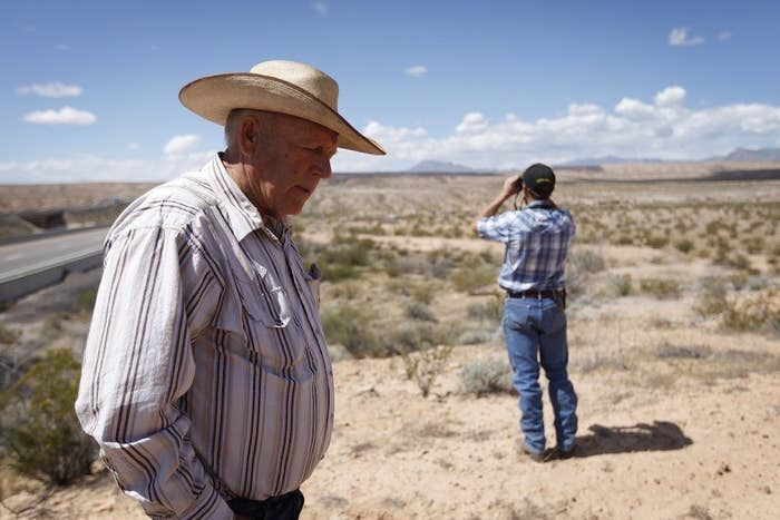 Cliven Bundy (left) and his son Mel Bundy stand on a hill overlooking an area where federal authorities are building corrals near Bunkerville, Nev., Tuesday.