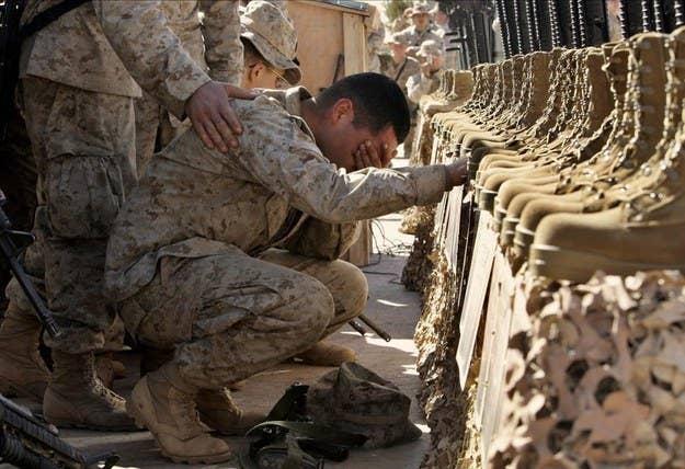 Um fuzileiro naval dos Estados Unidos chora durante um serviço memorial por 31 militares norte-americanos mortos perto de Rutbah, no oeste do Iraque.  2 de fevereiro de 2005.