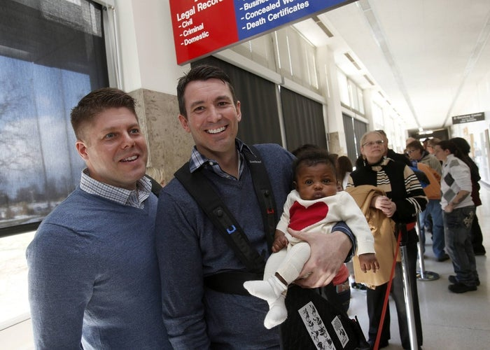Jim Schaffer (left) and his partner Jason McIntosh stand in line with their adopted baby Norah as they wait in line for a marriage license at the Oakland County Courthouse on March 22.