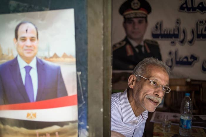 The owner of a cafe in Cairo sits beside a poster of Egypt's new president, Abdel Fattah al-Sisi.