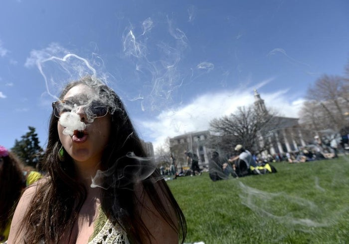 A woman blows marijuana smoke in Denver, Colo., April 20,