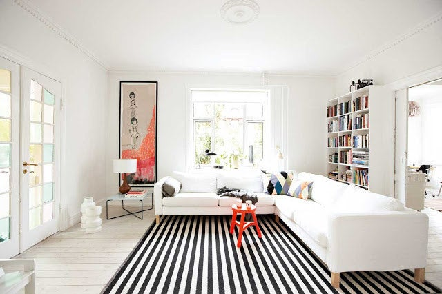 Just like vertical stripes on clothing, a striped rug will make your room appear longer. Orient the stripes to go the length of the room that is the longest for optimal effect.