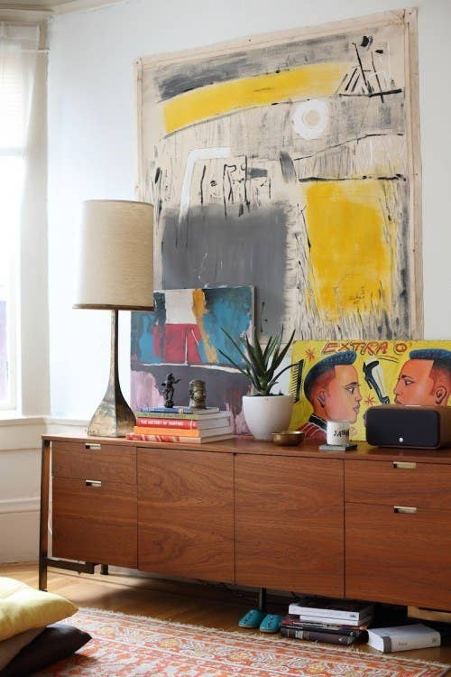 Instead of a gallery wall, choose art pieces that are large and bold. See more of this cool house here.