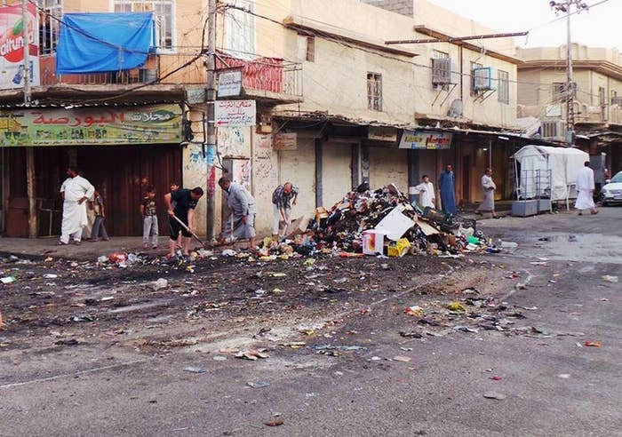 Residents clean up a street in the northern city of Mosul.