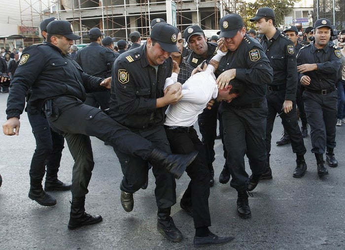 Police detain an opposition supporter in Baku, October 12, 2013.
