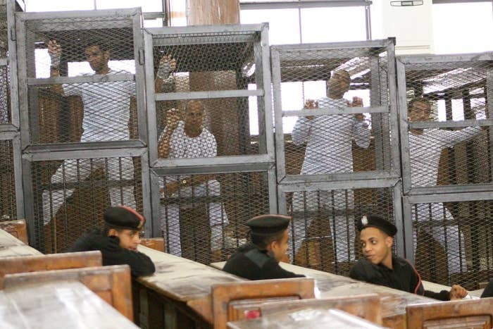 Defendants in the Al Jazeera trial stand in cages in an Egyptian court earlier this year.