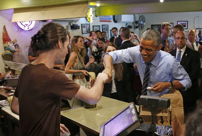 U.S. President Barack Obama fist bumps the cashier after paying for his order at Franklin Barbecue in Austin, Texas July 10, 2014.