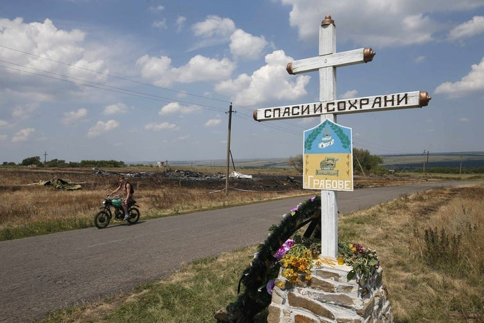 A local resident rides past near the village sign opposite the wreckage of Malaysia Airlines MH17.