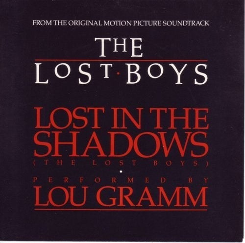 """Although """"Cry Little Sister"""" is the real theme from The Lost Boys – it says so in parentheses – this solo contribution from the onetime Foreigner frontman (he was still with the band at the time) is likely just as familiar to anyone who's seen the film. Although securing Lou Gramm for the soundtrack was no doubt made easier by the fact that he was already part of the Atlantic Records family, a 2012 Indiewire piece indicates that Schumacher helped seal the deal by promising to direct a video for Foreigner at some future juncture. Although it appears that Schumacher never made good on his promise, it would seem likely that the royalties Gramm has racked up over the years from writing """"Lost in the Shadows"""" would've helped heal any rift that might've occurred between them as a result of the reneging."""