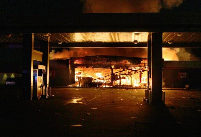 A QuikTrip convenience store burns after being looted Sunday during riots, which were sparked after a community candlelight vigil for Brown turned violent.
