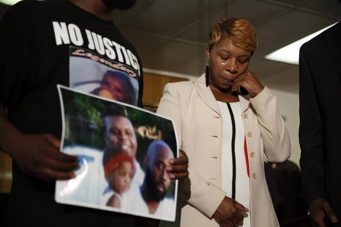 Lesley McSpadden, the mother of 18-year-old Michael Brown, wipes away tears as his father, Michael Brown Sr., holds up a family picture during a news conference in Jennings on Monday.