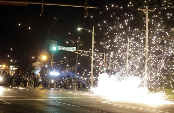 A device deployed by police goes off in the street as police and protesters clash Wednesday in Ferguson, Mo. Authorities in the St. Louis suburb where an unarmed black teen was shot and killed by a police officer have used tear gas to try to disperse protesters after flaming projectiles were thrown from the crowd.