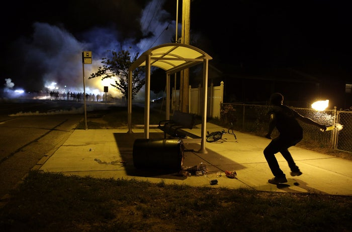A man picks up a flaming bottle and prepares to throw it as a line of police advances in the distance.