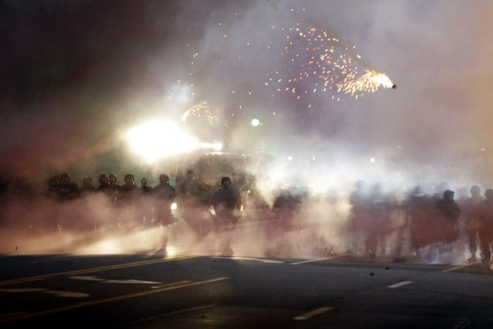 An explosive device deployed by police flies in the air as police and protesters clash Wednesday night.