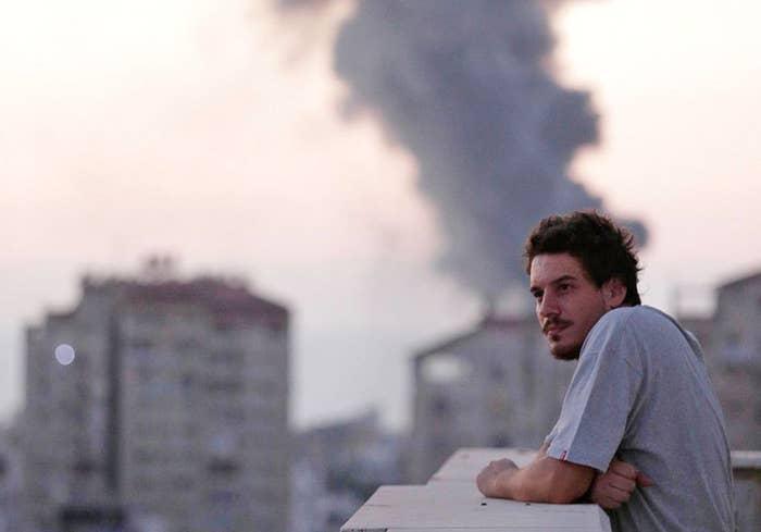 Associated Press video journalist Simone Camilli on a balcony overlooking smoke from Israeli strikes in Gaza City.
